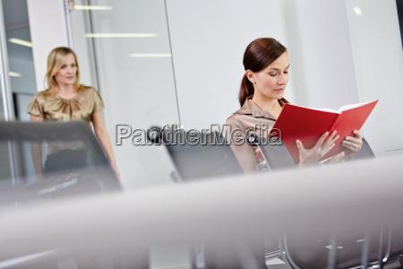 business-frau, saß, am, konferenztisch, lesebuch, kollegen, nähern - 19427176