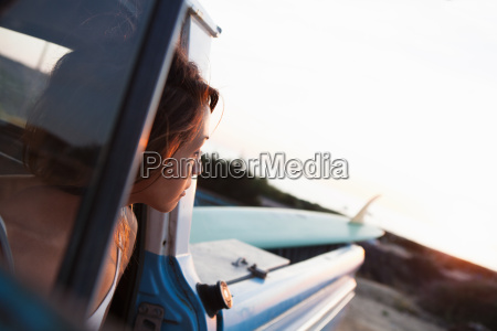 young female surfer looking from pick