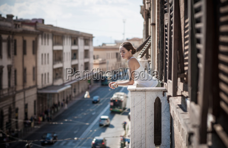 young woman looking over balcony onto
