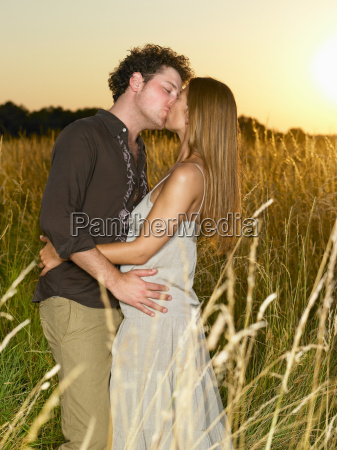 couple kissing in a field