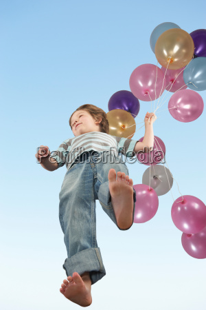 boy walking with bunch of balloons