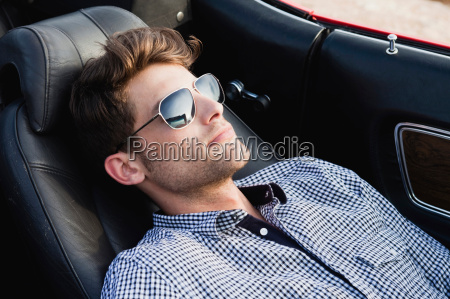 man lying in front seat of
