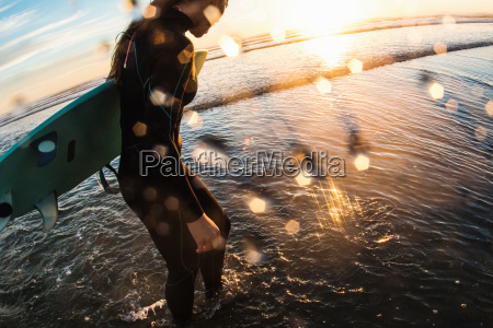 female surfer paddling in sea at