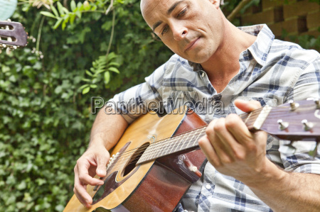 mid adult man playing acoustic guitar