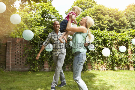 happy couple playing with toddler daughter