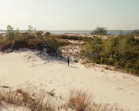 mid adult woman walking over sand