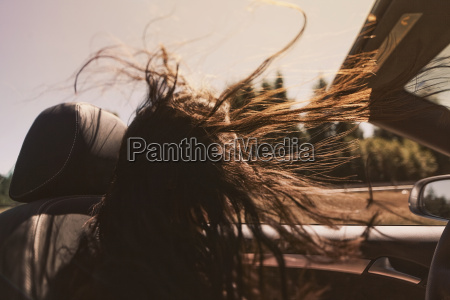 mid adult woman driving convertible with