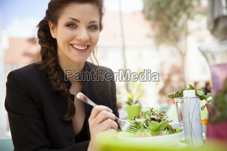young adult woman eating salad outside