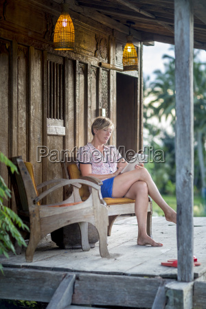 woman relaxing with digital tablet on