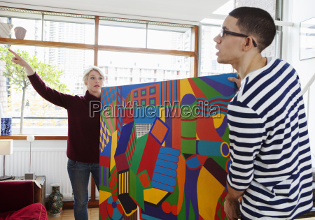young couple putting up painting in
