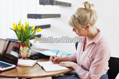 young woman sitting at table writing