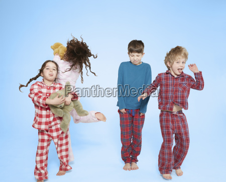 children in pyjamas dancing and jumping