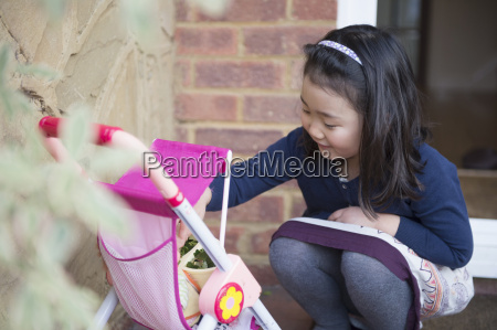 young girl playing with toy pushchair