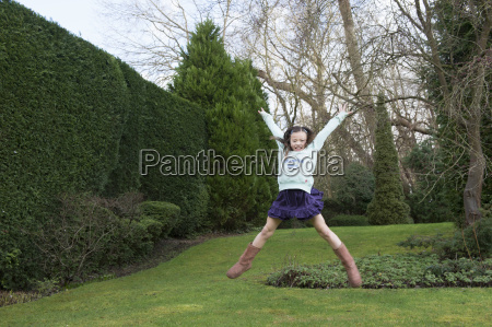 young girl jumping mid air in