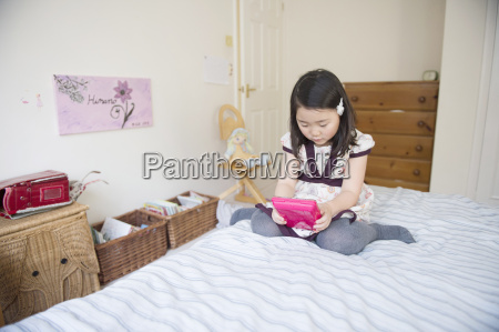 young girl sitting on bed playing