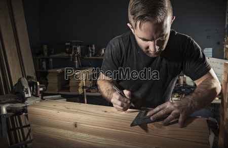 male carpenter measuring wooden plank with