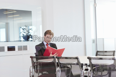 businessman sitting at conference room table