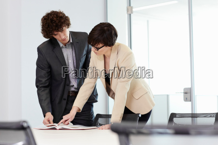 businesspeople standing at conference table pointing