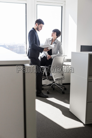 businesspeople standing in office looking at