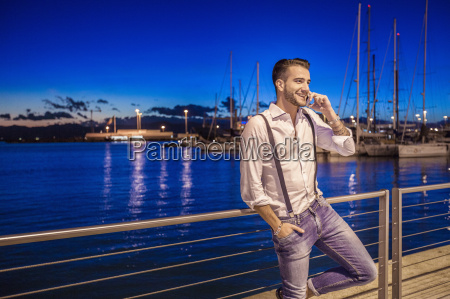 young man using smartphone by port
