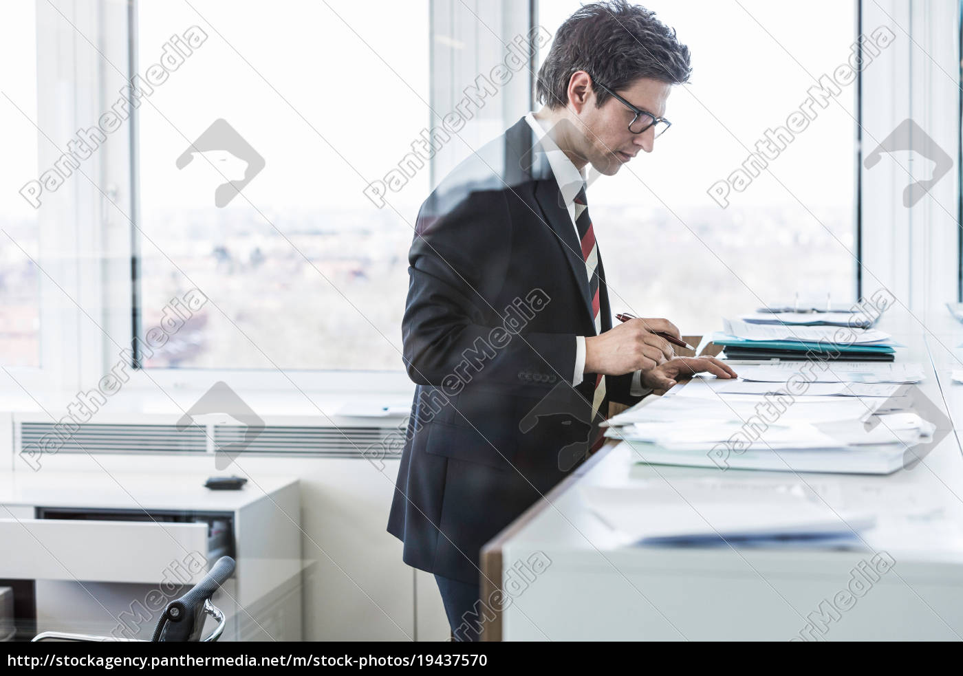 businessman, standing, in, office, looking, at - 19437570
