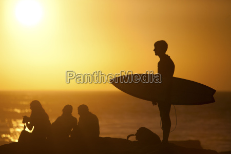 surfer carrying surfboard on beach at