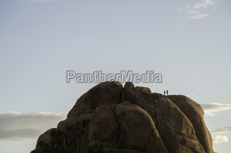 two people on high rock formation