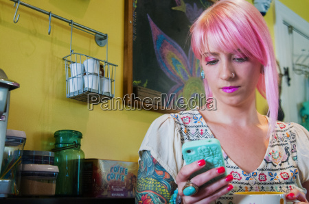 young woman with pink hair reading