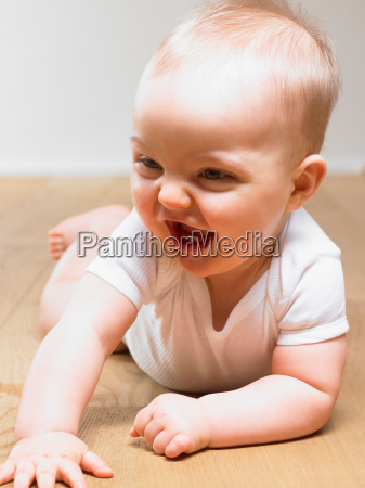 baby on the floor smiling