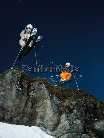 skiers jumping over rock