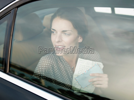 woman holding letter in backseat of