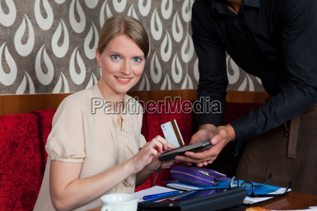 woman paying waiter with card in