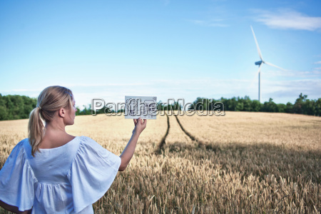 woman examining childs drawing in field