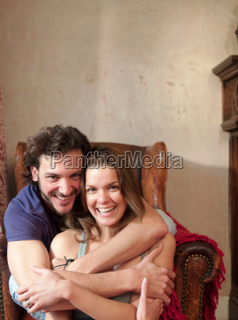 couple in old chair embraced laughing
