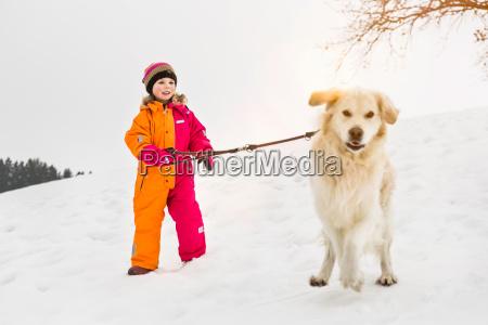 girl walking dog in snow