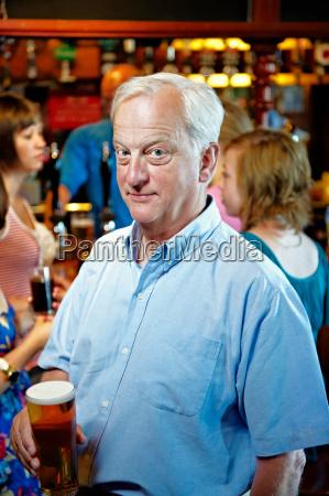 older man holding glass of beer