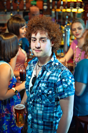 young man holding glass of beer