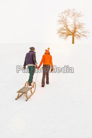 couple pulling toboggan in snow