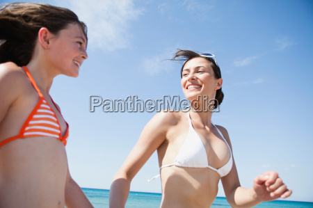 mother with daughter running along beach