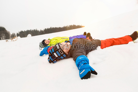 two boys making snow angels