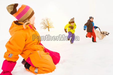 two boys running in snow with