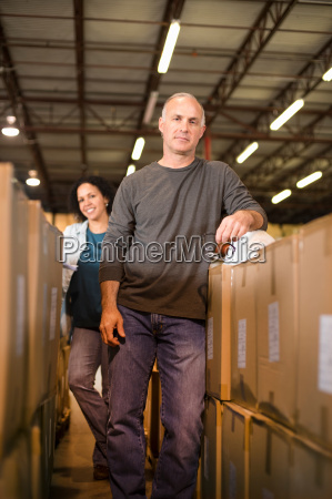 portrait of warehouse workers by cardboard