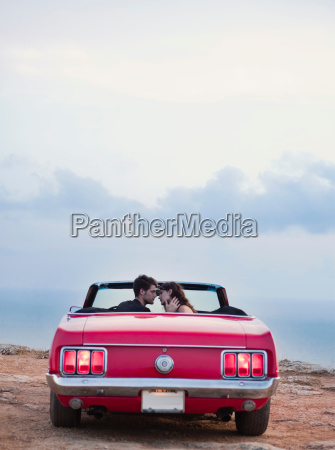 couple sitting in front of cabriolet