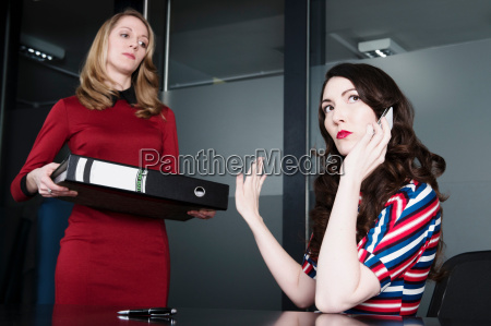 woman stopping colleague from interrupting telephone