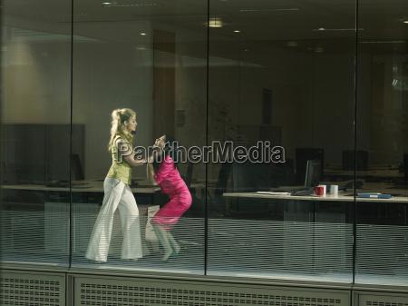 two women fighting in an office