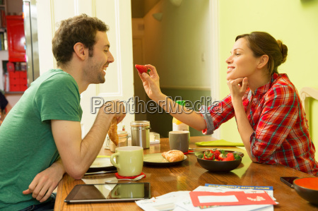 young couple at breakfast woman feeding