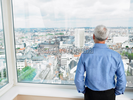 business man looking through window