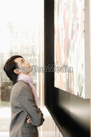 man looking at a painting