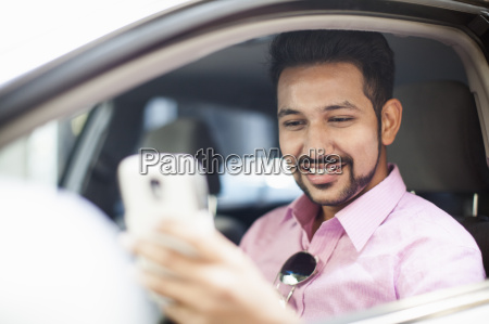 young businessman reading smartphone text at