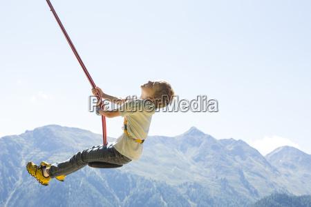 boy having fun on swing tyrol